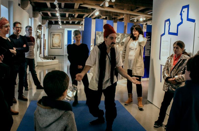 Imagen de un dinamizador con varias familias en el museo